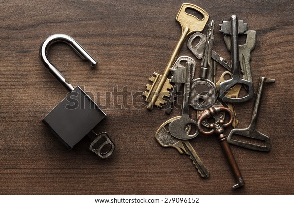 opened check-lock and different keys on wooden background concept