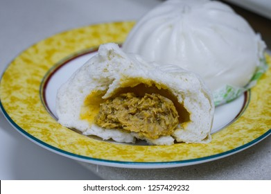 Opened Chinese Steamed Bun in a Plate, Showing Meat and Veggies Fillings Inside.