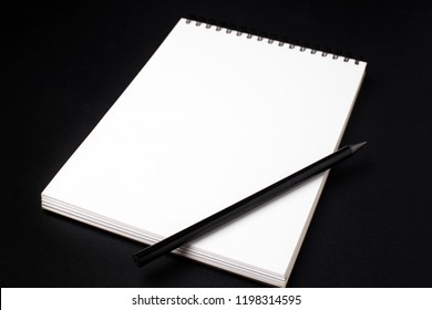 Opened clean notebook or sketchbook with pencil on black background