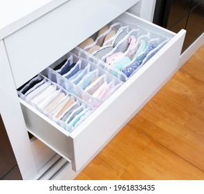 The opened closet drawer with fabric boxes for separate storage of bra and underwear.