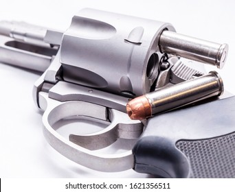 The opened cylinder of a stainless 357 magnum revolver with a hollow point bullet laying upon it and one protruding from the gun