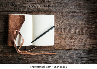 An opened diary leather book with blank space on the wood table. The education and learning concept.