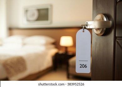 Photo of Opened door of hotel room with key in the lock