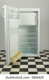 Opened, empty fridge, standing on black and white floor. Front view