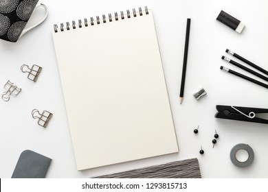 Opened empty sketchbook mockup on the desk. Top view real photo. A black and white concept desk with a mess of office supplies. Blank white background with space for text