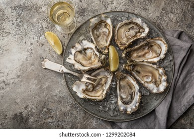 opened fresh raw oysters on gray plate served with lemon and white wine, top view, concrete background