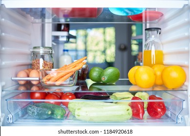 Opened fridge from the inside full of vegetables, fruits and other groceries.