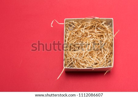 Opened gift box with decorative fillers on red background