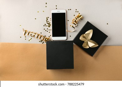 Opened gift box and smartphone on color background, top view