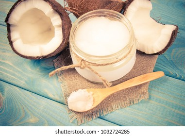 Opened glass jar with fresh coconut oil on wooden background.