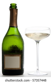An opened green bottle of champagne (with a blank label) next to a saucer style champagne glass.  Studio isolated on a white background.