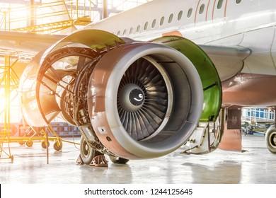 Opened hood aircraft engine jet under maintenance in the hangar