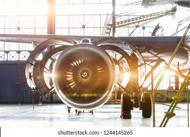 Opened hood airplane engine jet under maintenance in the hangar ,with bright light flare at the gate