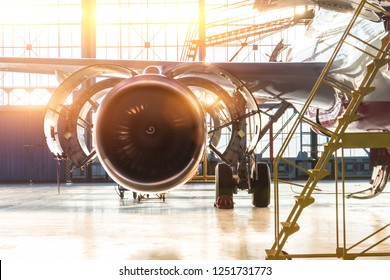 Opened hood airplane engine jet maintenance in the hangar stairs ,with bright light flare at the gate