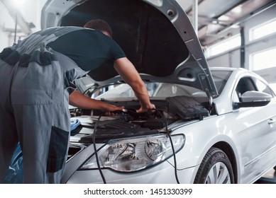 Opened hood. Man in grey uniform repairs white automobile indoors.