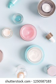 Opened jars of face creams of different colors and sizes on blue background.