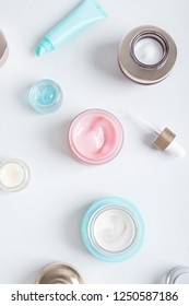Opened jars of face creams of different colors and sizes on gray background.