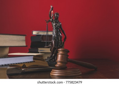opened juridical books with lady justice statue and gavel on wooden table, law concept