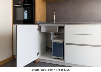 Opened kitchen cabinet with sink and installed garbage bin, smart solution for kitchen design. Kitchen in a modern loft style in white, grey and wooden details.