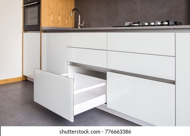 Opened kitchen drawer, kitchen in a modern loft style with wooden elements, grey countertop and backsplash.