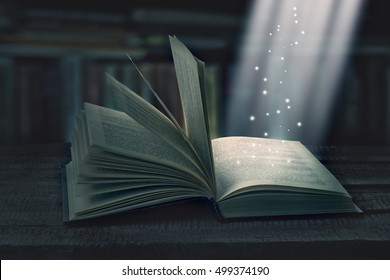 Opened magic book with magic light on a wooden table with bookshelf, invitation to study literatures. The magic of reading or bible and religion. Concept of religion. Christmas fairy-tale.