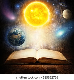 Opened magic book with sun, earth, moon, saturn, stars and galaxy. Concept on the topic of astronomy or fantasy. Elements of this image furnished by NASA.