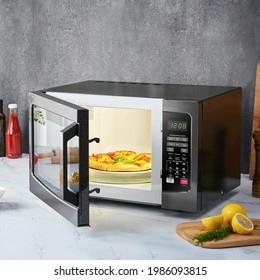 Opened microwave on kitchen table with pizza