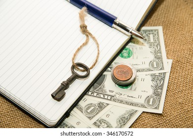 Opened notebook with a blank sheet, pen and money on the old tissue