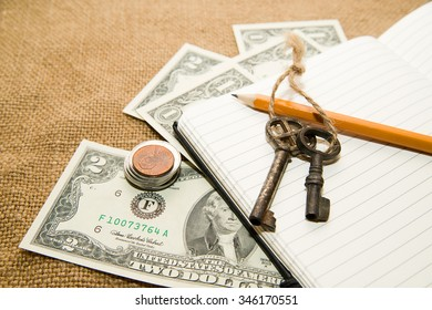 Opened notebook with a blank sheet, pencil, keys and money on the old tissue