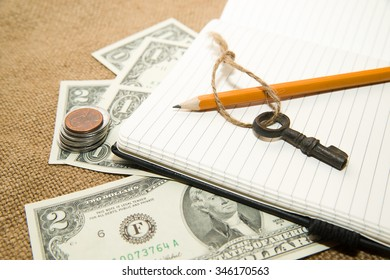 Opened notebook with a blank sheet, pencil and money on the old tissue