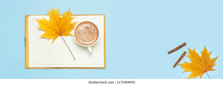 Opened notebook, cocoa latte or coffee in cup, yellow autumn maple leaf on blue background top view flat lay. Autumn or winter hot drink, concept of study, working table. Long banner Space for text