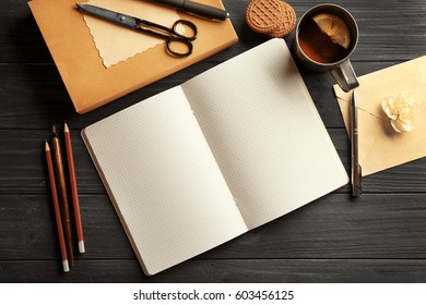 Opened notebook and cup of tea on wooden table