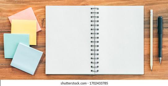 Geöffnetes Notizbuch mit doppelter leerer Seite mit Stift, Stift und Notizblock auf Holztisch.