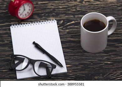 Opened notebook, glasses ,mug, pen and red alarm clock