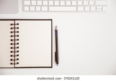 Opened notebook, keyboard on the table, workplace background