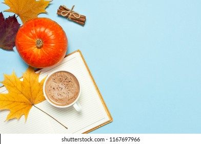 Opened notebook, orange pumpkin, pumpkin spiced latte or coffee in cup, cinnamon, yellow autumn maple leaf on blue background top view flat lay. Autumn or winter hot drink, halloween concept.