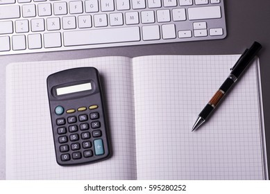 Opened notebook with a pen and calculator on top, and next to a mouse and a keyboard of a computer.