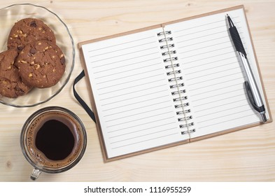 Opened notebook with pen, transparent cup of coffee and chocolate chip cookies on a light wooden table background, top view