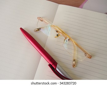Opened  notebook, red ink pen, pink glasses