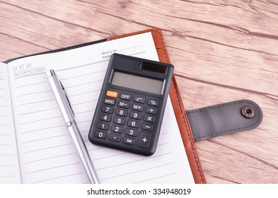 Opened notepad with blank area for text or message, pen, and calculator on wood table