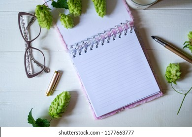 The opened notepad, pen, white candle, glasses and branches of hops as decoration on a white wooden table. Desktop still life with space for text.