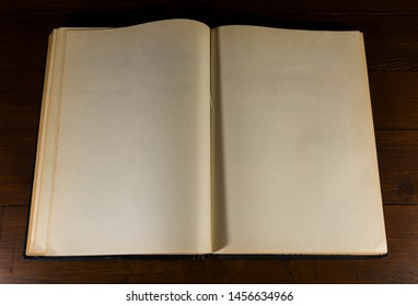 Opened ,old, aged , yellow, blank book pages on dark brown wood background.