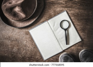 Opened old blank book with magnifying glass. Detective hat and shoes on brown background. Retro things. Historical atmosphere. Vintage english style. Evidence searching concept. Empty place for text.