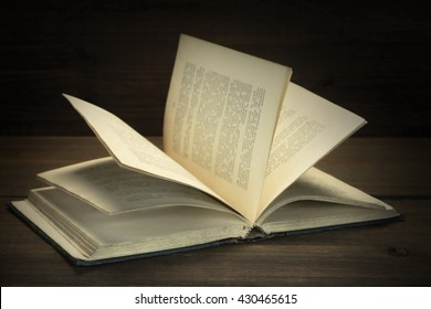 Opened Old Shabby Book With Blurred Text On The Grunge  Rough Wood Background, Close Up