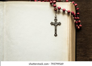 Opened old thick bible with crucifix on the brown table in the quiet, dark atmosphere. Prayer time on sunday. Empty place for text. Religion concept.