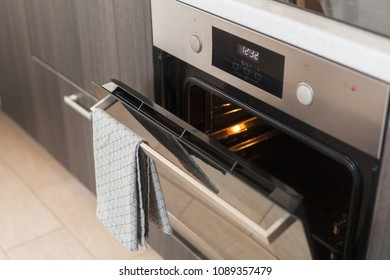 Opened oven with grey towel hanging on it