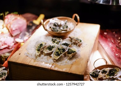 opened oyster with garlic and herbs and cheese offered as top view on wood table