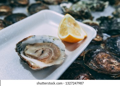 Opened oyster shell with lemon juice served on the street open market. Man Hand squeezing the lemon on the seafood