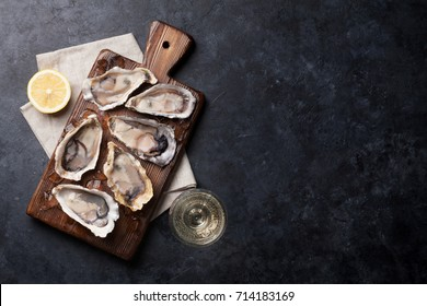Opened oysters, ice and lemon on board and white wine on stone table. Top view with copy space