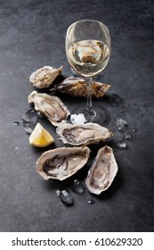 Opened oysters, ice and lemon with white wine over stone table. Half dozen